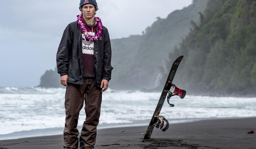 In this Feb. 21, 2017, photo provided by Red Bull, Lyon Farrell poses on a beach in Waipo Valley on the island of Hawaii. Farrell grew up skateboarding and surfing in Hawaii before a visit to New Zealand introduced him to snowboarding. Ever since, he's preferred landing triple corks to hanging 10 as he sets his sights on making the U.S. slopestyle squad for the Olympics next winter in South Korea.  (Zak Noyle/Red Bull via AP)
