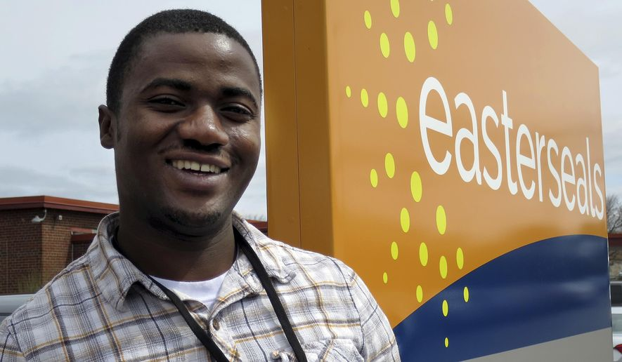 In this April 13, 2017 photo, Ombeni Kasongo poses outside the Easterseals office in Manchester, N.H. Kasongo, a native of the Democratic Republic of Congo, is among 11 immigrants and refugees being trained to work in a residential treatment facility for children with neurological, psychological and behavioral challenges. (AP Photo/Holly Ramer)