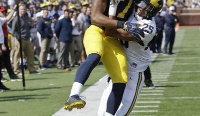 Michigan defensive back Benjamin St-Juste (25) interferes with receiver Tarik Black (7) during the Michigan NCAA college spring football game, Saturday, April 15, 2017, in Ann Arbor, Mich. (AP Photo/Carlos Osorio)