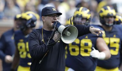 Michigan head coach Jim Harbaugh talks to his players during the NCAA college football team's spring game Saturday, April 15, 2017, in Ann Arbor, Mich. (AP Photo/Carlos Osorio)