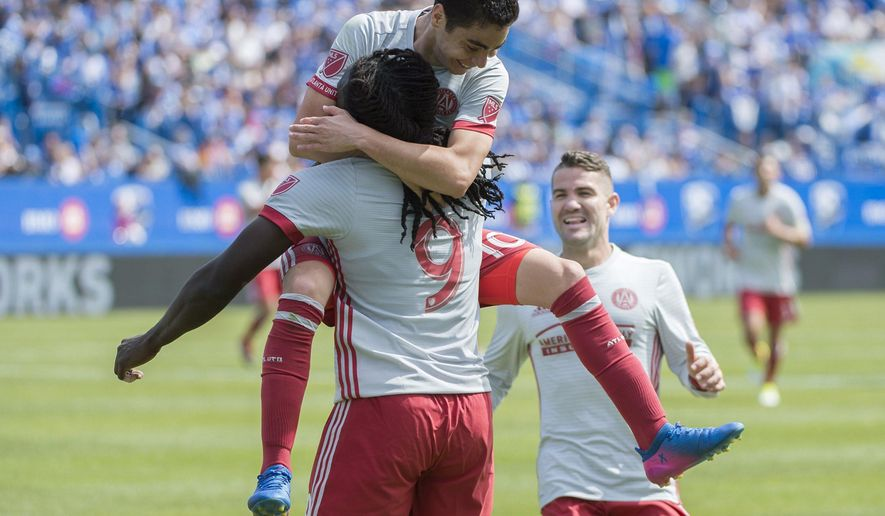Atlanta United's Kenwyne Jones (9) celebrates with teammates Miguel Almiron (10) and Greg Garza (4) after scoring during the first half of an MLS soccer game against the Montreal Impact, in Montreal, Saturday, April 15, 2017. (Graham Hughes/The Canadian Press via AP)