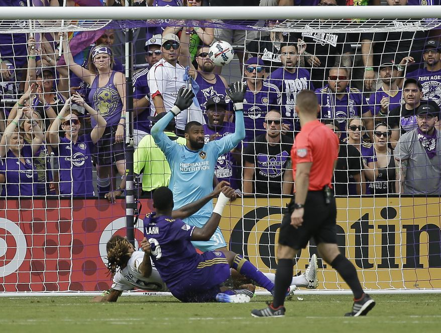 Orlando City's Cyle Larin (9) scores a goal as he shoots the ball over Los Angeles Galaxy goalkeeper Clement Diop, back center, during the second half of an MLS soccer game, Saturday, April 15, 2017, in Orlando, Fla. (AP Photo/John Raoux)