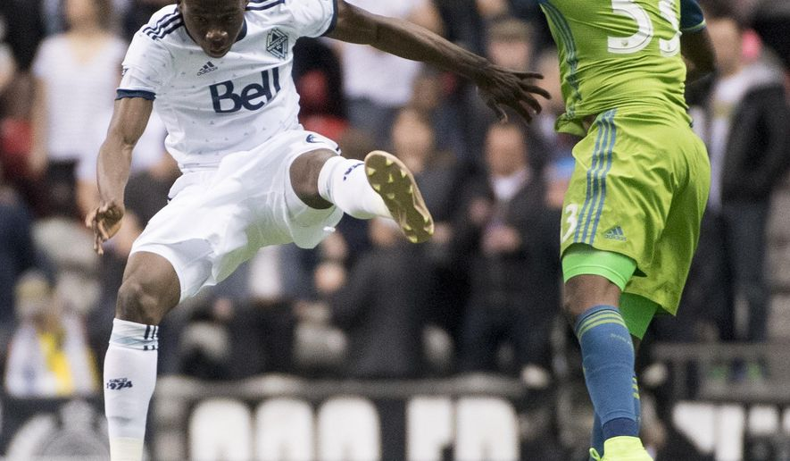 Vancouver Whitecaps' Alphonso Davies, left, fights for control of the ball with Seattle Sounders' Joevin Jones during the first half of an MLS soccer game in Vancouver, British Columbia, Friday, April 14, 2017. (Jonathan Hayward/The Canadian Press via AP)