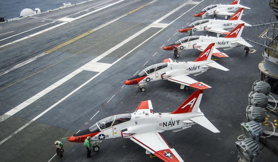 FILE - In this Dec. 10, 2016 file photo, pilots perform pre-flight procedures in T-45C Goshawks from Training Air Wing One on the flight deck of the aircraft carrier USS George Washington docked in Norfolk, Va. A fleet of U.S. Navy training jets will fly again after oxygen problems grounded the planes for more than a week. Vice Adm. Mike Shoemaker said in a statement Saturday, April 15, 2017, that T-45C aircraft will resume flights as early as Monday. (Petty Officer 2nd Class Bryan Mai/U.S. Navy via AP, File)