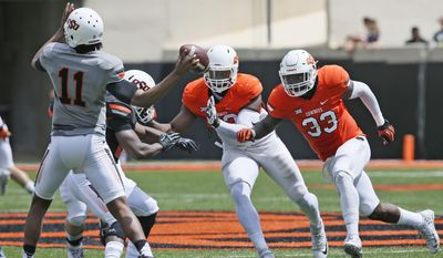 Oklahoma State linebacker Kevin Henry (33) and defensive end Jarrell Owens, center, pressure quarterback Keondre Wudtee (11) during an intra squad spring NCAA college football game in Stillwater, Okla., Saturday, April 15, 2017. (AP Photo/Sue Ogrocki)