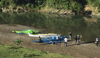 FILE - This undated photo provided by the Armed Forces of the Philippines on April 12, 2017, shows people stand by boats which the military said were used by Abu Sayyaf militants to enter the Ibananga River in Bohol province, central Philippines, as government troopers continue clearing operations. Philippine officials said Saturday, April 15, 2017, that an investigation shows that a foiled attack on a resort island this week was a kidnapping and bombing mission by at least three nascent groups affiliated with the Islamic State group. (3rd ID, Armed Forces of the Philippines via AP, File)