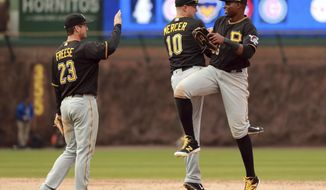 Pittsburgh Pirates shortstop Jordy Mercer (10) and left fielder Gregory Polanco (25) celebrate after defeating the Chicago Cubs as teammate David Freese (23) waits to high-five after a baseball game in Chicago, on Friday, April 14, 2017. (AP Photo/Jeff Haynes)