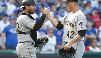Pittsburgh Pirates' Francisco Cervelli, left, celebrates with Tony Watson, right, their win over the Chicago Cubs, Saturday, April 15, 2017, in Chicago. (AP Photo/Kamil Krzaczynski)
