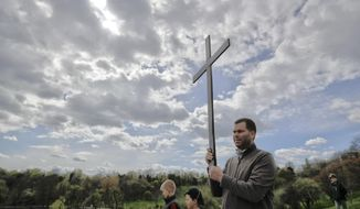 In this Saturday, April 8, 2017, picture a Romanian Catholic holds a wooden cross during a procession ahead of Palm Sunday in Bucharest, Romania. Ahead of Easter, celebrated by both Orthodox and Catholic believers on April 16 processions of priests clad in golden robes carrying foliage on Palm Sunday in a recreation of Jesus' ride into Jerusalem, mixed with more commercial flavored celebrations like an Easter fair outside the giant palace built by late Communist leader Nicolae Ceausescu where entertainers strutted around wearing giant rabbit heads.(AP Photo/Vadim Ghirda)