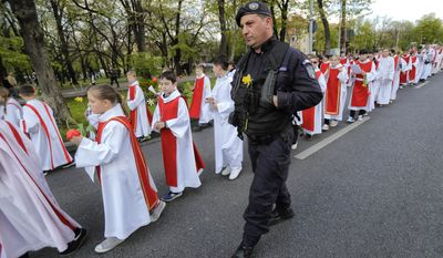 In this Sunday, April 9, 2017, picture a gendarme with a flowers attached to his uniform walks next to Catholic children taking part in a Palm Sunday procession in Bucharest, Romania. Ahead of Easter, celebrated by both Orthodox and Catholic believers on April 16 processions of priests clad in golden robes carrying foliage on Palm Sunday in a recreation of Jesus' ride into Jerusalem, mixed with more commercial flavored celebrations like an Easter fair outside the giant palace built by late Communist leader Nicolae Ceausescu where entertainers strutted around wearing giant rabbit heads.(AP Photo/Vadim Ghirda)