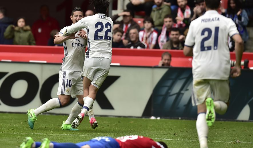 Real Madrid's Isco, center, celebrates with James Rodriguez after scoring the third goal against Sporting de Gijon during the Spanish La Liga soccer match between Real Madrid and Sporting de Gijon, at El Molinon stadium in Gijon, northern Spain, Saturday, April 15, 2017. Real Madrid won the match 3-2. (AP Photo/Alvaro Barrientos)