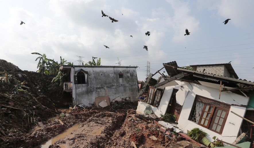 Crows fly over a row of houses buried by a collapse of a garbage dump in Meetotamulla, on the outskirts of Colombo, Sri Lanka, Saturday, April 15, 2017. A part of the garbage dump that had been used in recent years to dump the waste from capital Colombo collapsed destroying houses, according to local media reports. (AP Photo/Eranga Jayawardena)