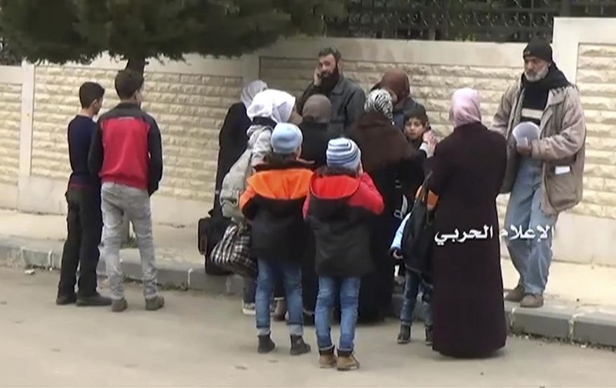 This frame grab from video provided by the government-controlled Syrian Central Military Media  shows Syrian families gathering to leave in buses from Madaya, an opposition-held town near Damascus, Syria, Friday, April 14, 2017. The Syrian government and rebels began a coordinated population transfer Friday of about 10,000 people from four towns besieged for years amid the country's bloody, six-year civil war. (Syrian Central Military Media, via AP)