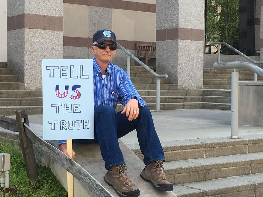 Mike Mannshardt, 70, a retired teacher from Pittsboro, N.C., waits to hear from speakers at an anti-Trump rally in Raleigh  on Saturday, April 15, 2017. Mannshardt and other demonstrators want Trump to release his income tax returns. (AP Photo/ Emery P. Dalesio)
