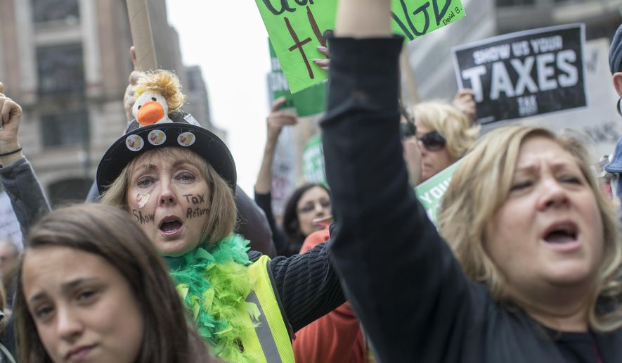 Demonstrators participate in a march and rally to demand President Donald Trump release his tax returns, Saturday, April 15, 2017, in New York.  Protesters took to the streets in dozens of cities nationwide Saturday to call on President Donald Trump to release his tax returns, saying Americans deserve to know about his business ties and potential conflicts of interest.  (AP Photo/Mary Altaffer)