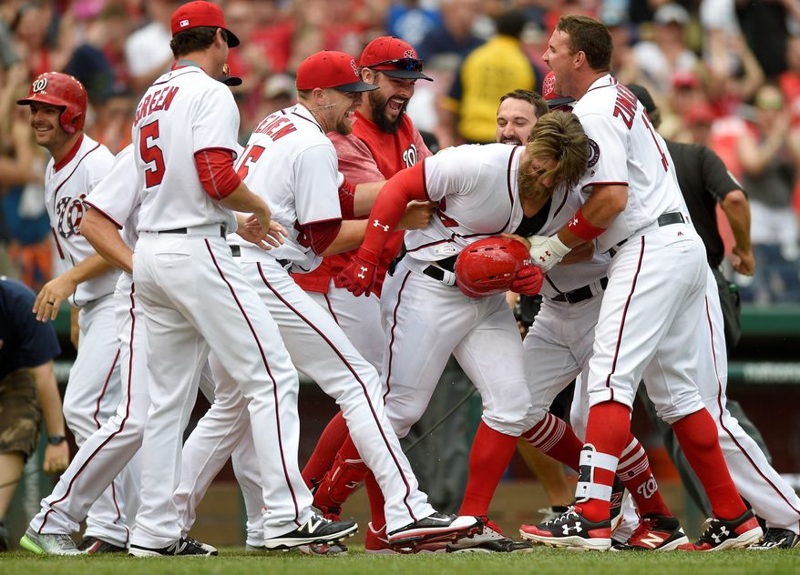 Washington Nationals' Bryce Harper, second from right, is mobbed by teammates after a baseball game against the Philadelphia Phillies, Sunday, April 16, 2017, in Washington. Harper hit a three-run walkout home run. The Nationals won 6-4. (AP Photo/Nick Wass)