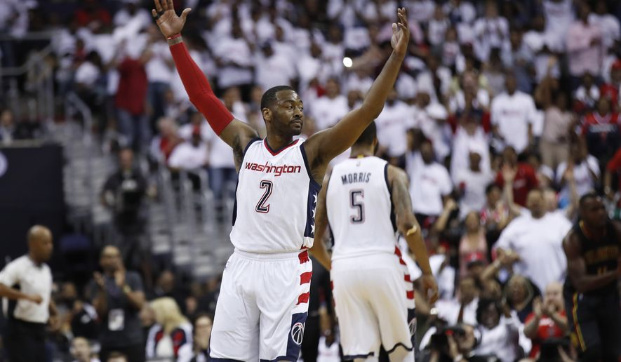 Washington Wizards guard John Wall (2) reacts to the cheering Wizards fans during the second half in Game 1 of a first-round NBA basketball playoff series, in Washington, Sunday, April 16, 2017. The Wizards won 114-107.  (AP Photo/Manuel Balce Ceneta)