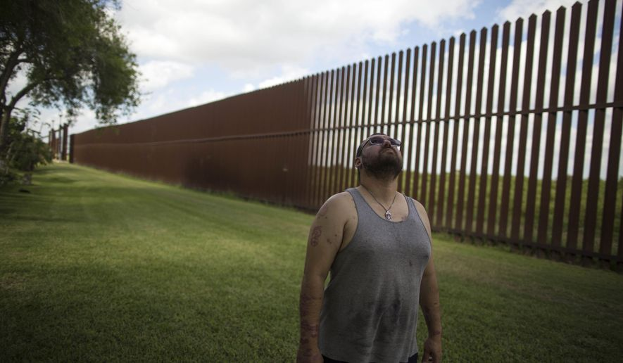 "In this March 22, 2017, file photo, Antonio Reyes of Brownsville, Texas, stands by the U.S.-Mexico border fence near his home. Reyes said he's seen people scale the border fence that bisects his backyard and jump down in seconds. Sometimes they carry bales of what appear to be drugs. A higher wall is ""still not going to stop them,"" he said. ""They'll shotput it or whatever they have to do."" (AP Photo/Rodrigo Abd, File)"