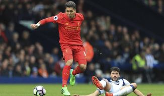 Liverpool's Roberto Firmino, left, and West Bromwich Albion's Claudio Yacob in action during their English Premier League soccer match at The Hawthorns, West Bromwich, England, Sunday, April 16, 2017. (Adam Davy/PA via AP)