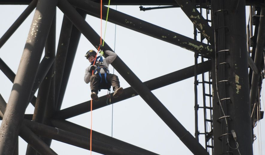 In this Thursday, April 13, 2017 photo, Shaun Golden, a firefighter with the Hamilton Township Fire Department repels from an upper deck of the Battleship New Jersey as he takes part in NSR Solutions LLC and Med-Tech's Confined Space Training classes aboard the battleship, at the Battleship New Jersey Memorial and Museum, in Camden, N.J. (Chris LaChall /Camden Courier-Post via AP)