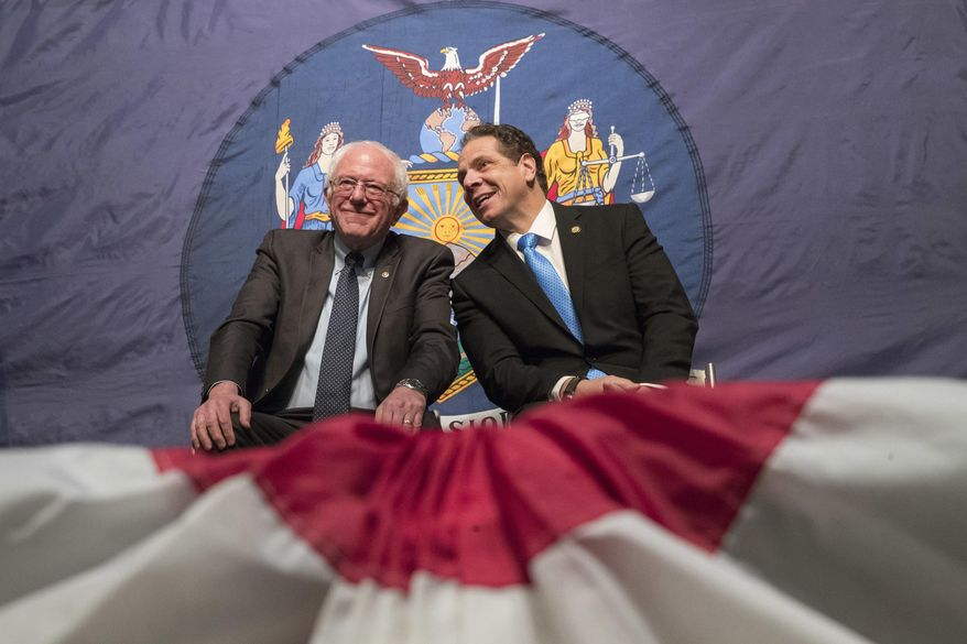 "FILE - In this Jan. 3, 2017, file photo, New York Gov. Andrew Cuomo, right, and Vermont Sen. Bernie Sanders appear onstage together during an event at New York's LaGuardia Community College. It's the hope of proponents such as Sanders and Hillary Clinton, who made debt-free college a key talking point in their Democratic presidential campaigns, that New York's first-in-the-nation free tuition program for middle-class students will spread to other states. And that's the prediction of Cuomo, its main champion, who called the plan a ""model for the nation."" (AP Photo/Mary Altaffer, File)"