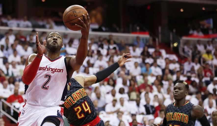 Washington Wizards guard John Wall (2) shoots past Atlanta Hawks forward Kent Bazemore (24) and Dennis Schroder (17) during the first half in Game 1 of a first-round NBA basketball playoff series, in Washington, Sunday, April 16, 2017. The Wizards won 114-107. AP Photo/Manuel Balce Ceneta)