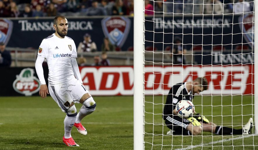 Real Salt Lake forward Yura Movsisyan, let, runs to the net to retrieve the ball after scoring a goal on a penalty kick past Colorado Rapids goalkeeper Zac MacMath in the second half of an MLS soccer match Saturday, April 15, 2017, in Commerce City, Colo. (AP Photo/David Zalubowski)