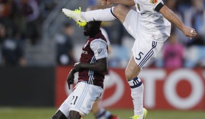 Real Salt Lake midfielder Kyle Beckerman, front, kicks the ball over Colorado Rapids defender Bismark Adjei-Boateng in the first half of an MLS soccer match, Saturday, April 15, 2017, in Commerce City, Colo. (AP Photo/David Zalubowski)