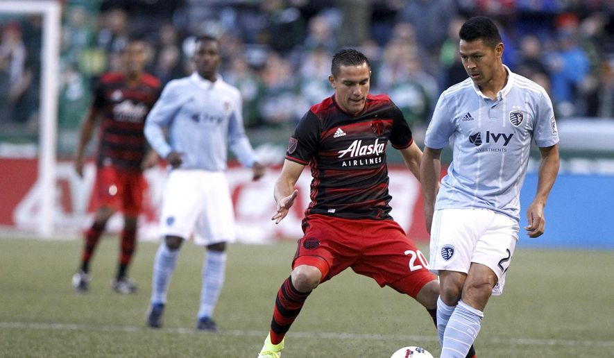 Sporting Kansas City's Roger Espinoza (27) looks to keep possession as Portland Timbers' David Guzman (20) defends during an MLS soccer match Saturday, April 15, 2017, in Portland, Ore. (Sean Meagher/The Oregonian via AP)