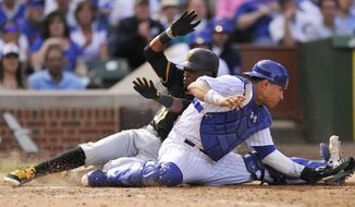 Chicago Cubs catcher Willson Contreras attempts to force out Pittsburgh Pirates' Alen Hanson (37) as he slides safely into home plate after Andrew McCutchen grounded into a fielders choice during the eighth inning of a baseball game, Sunday, April 16, 2017, in Chicago. (AP Photo/Paul Beaty)