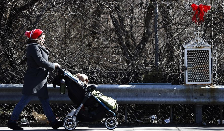 In a photo taken Wednesday, March 22, 2017, in Jersey City, N.J., a woman pushes a stroller near a roadside memorial on Newark Avenue. As roadside memorials to people killed in accidents and fires become more common, officials across the nation are raising their concerns. They want standards set for the makeshift sites, fearing they will become eyesores or traffic hazards. But grieving family and friends want the sites left alone, questioning why government needs to be involved in personal matters. (AP Photo/Julio Cortez)