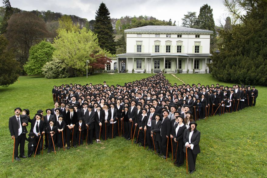 """662 people dressed as Charlie Chaplin pose for a group photo in front of the Manoir de Ban during an attempt of the world's largest gathering of people dressed as The Tramp on the occasion of Charlie Chaplin's birthday, and to celebrate the first year of the museum """"Chaplin's World by Grevin"""", in Corsier-sur-Vevey, Switzerland, Sunday, April 16, 2017.  (Laurent Gillieron/Keystone via AP)"""