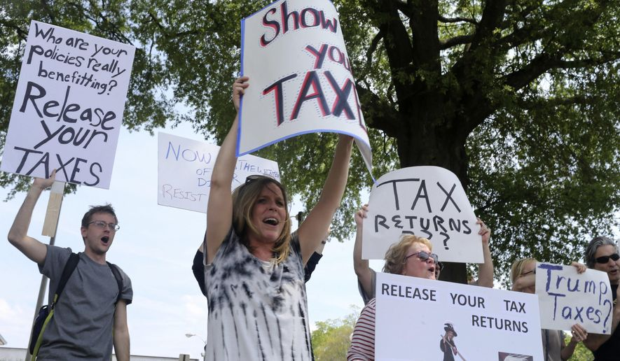Demonstrators hold signs at the during a Tax Day protest in Florence, Ala. Members of Indivisible NW Alabama gathered to voice their request that President Donald Trump release his tax returns. (Allison Carter/The TimesDaily via AP)
