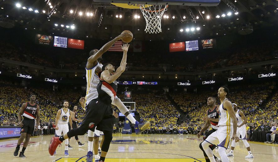 Portland Trail Blazers guard C.J. McCollum, foreground, shoots in front of Golden State Warriors forward Kevin Durant during the first half of Game 1 of a first-round NBA basketball playoff series in Oakland, Calif., Sunday, April 16, 2017. (AP Photo/Jeff Chiu)