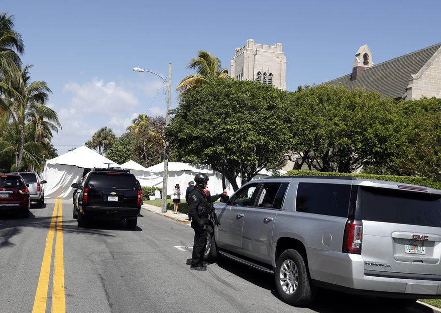 President Donald Trump's motorcade is seen in front of the Episcopal Church of Bethesda-by-the-Sea where Trump and his family are attending Easter services, Sunday, April 16, 2017, in Palm Beach, Fla. (AP Photo/Alex Brandon)