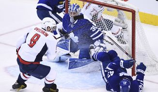Toronto Maple Leafs goalie Frederik Andersen (31) looks on as Washington Capitals left wing Alex Ovechkin (8) and Toronto Maple Leafs center Nazem Kadri (43) battle in front during the first period in Game 3 of an NHL Stanley Cup first-round playoff series in Toronto on Monday, April 17, 2017. (Frank Gunn/The Canadian Press via AP)