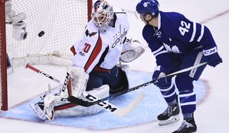 Washington Capitals goalie Braden Holtby (70) makes a save on Toronto Maple Leafs center Tyler Bozak (42) during first period NHL hockey round one playoff action in Toronto on Monday, April 17, 2017. (Frank Gunn/The Canadian Press via AP)