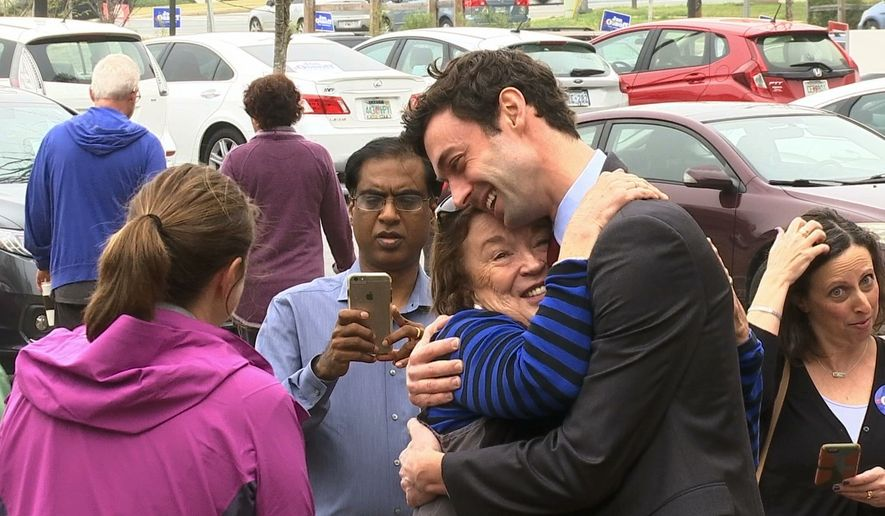 """In a Monday, March 27, 2017, file photo, Democratic Congressional candidate Jon Ossoff greets supporters outside of the East Roswell Branch Library in Roswell, Ga., on the first day of early voting. President Donald Trump is attacking the leading Democratic candidate for a special election in a typically conservative Georgia congressional district, with Republicans bidding to avoid a major upset. On Twitter, Trump said Monday April 17, 2017, that """"The super Liberal Democrat in the Georgia Congressional race tomorrow wants to protect criminals, allow illegal immigration and raise taxes!"""" (AP Photo/Alex Sanz)"""