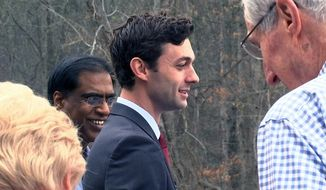 "In a Monday, March 27, 2017 photo, Democratic congressional candidate Jon Ossoff is seen with supporters outside of the East Roswell Branch Library in Roswell, Ga., on the first day of early voting.  President Donald Trump is attacking Ossoff, the leading Democratic candidate for a special election in a typically conservative Georgia congressional district, with Republicans bidding to avoid a major upset. On Twitter, Trump said Monday April 17, 2017, that ""The super Liberal Democrat in the Georgia Congressional race tomorrow wants to protect criminals, allow illegal immigration and raise taxes!"" (AP Photo/Alex Sanz)"