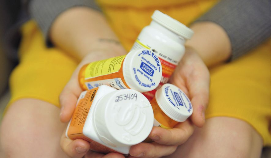 Heidi Wyandt, 27, holds a handful of her medication bottles at the Altoona Center for Clinical Research in Altoona, Pa., on Wednesday, March 29, 2017, where she is helping test an experimental non-opioid pain medication for chronic back pain related to a work related injury she received in 2014. With about 2 million Americans hooked on opioid painkillers, researchers and drug companies are searching for less addictive drugs to treat pain. (AP Photo/Chris Post)