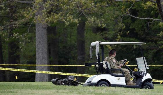 Investigators examine debris that fell on the Breton Bay Golf and Country Club after an Army UH-60 helicopter from Fort Belvoir, Va., crashed, Monday, April 17, 2017, in Leonardtown, Md. (AP Photo/Alex Brandon)