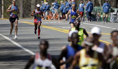 Luke Puskedra, left, Meb Keflezighi and Jared Ward, all of the United States, run behind the leaders in the 121st Boston Marathon on Monday, April 17, 2017, in Natick, Mass. (AP Photo/Steven Senne)