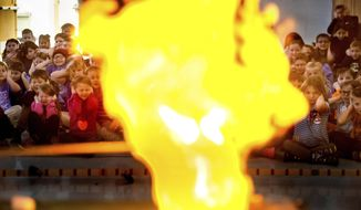 In this Feb. 24, 2017 photo, Starke Primary School students in Pekin, Ill., react as a  hydrogen balloon is ignited by the Demo Crew, which is composed of students from Bradley University's Chemistry Club. Led by chemistry professor Dean Campbell, the program has been presented for more than 20,000 people, primarily middle school students to share an appreciation of science.(Fred Zwicky/Journal Star via AP)