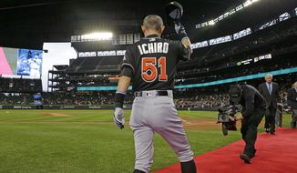 Miami Marlins' Ichiro Suzuki tips his cap after being honored by Seattle Mariners players and executives for his 3,000 hit milestone in a pre-game ceremony before a baseball game against the Mariners, his former team, Monday, April 17, 2017, in Seattle. (AP Photo/Ted S. Warren)