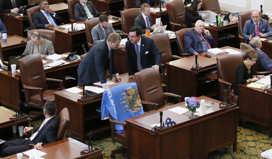 The empty chair of Oklahoma state Rep. David Brumbaugh, R-Broken Arrow, is draped with a state flag on the floor of the House in Oklahoma City, Monday, April 17, 2017. Brumbaugh, 56, died at his home Saturday, April 15, 2017. (AP Photo/Sue Ogrocki)
