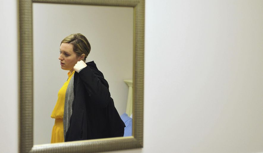 Heidi Wyandt, 27, puts on her coat to leave the Altoona Center for Clinical Research in Altoona, Pa., on Wednesday, March 29, 2017, where she is helping test an experimental non-opioid pain medication for chronic back pain related to a work related injury she received in 2014. With about 2 million Americans hooked on opioid painkillers, researchers and drug companies are searching for less addictive drugs to treat pain. (AP Photo/Chris Post)