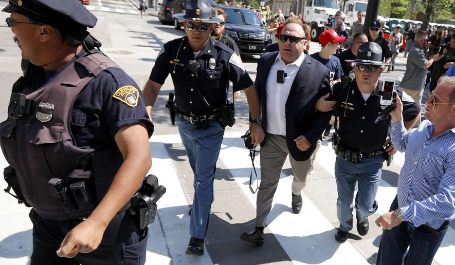 """FILE - In this file photo made Tuesday, July 19, 2016, Alex Jones, center right, is escorted by police out of a crowd of protesters outside the Republican convention in Cleveland. A lawyer defending Jones, a the right-wing radio host and conspiracy theorist, in a child-custody dispute said Jones is a """"performance artist"""" whose on-air persona differs from the private man. The Austin American-Statesman reported that Kelly Jones described her ex-husband at a recent pretrial hearing in Austin as """"not a stable person."""" (AP Photo/John Minchillo, File)"""