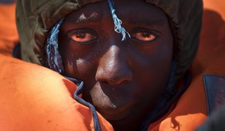 FILE - In this April 6, 2017 file photo, a migrant rescued from a rubber boat by members of Proactiva Open Arms NGO, in the Mediterranean sea, about 56 miles north of Sabratha, Libya. Most migrants on the Mediterranean are now trying to reach Italy. Those numbers have dramatically increased since the European Union and Turkey signed an agreement last year that allowed Greece to send new asylum-seekers back to Turkey. (AP Photo/Bernat Armangue, File)