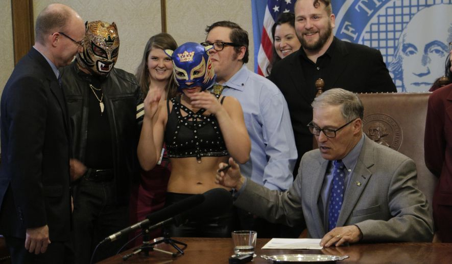 Washington Gov. Jay Inslee talks with supporters of theatrical wrestling before signing a bill that creates a license for theatrical wrestling schools, on Monday, April 17, 2017 in Olympia, Wash. Under the measure, any licensed theatrical wrestling school would be allowed to schedule a certain number of public performances. (AP Photo/Rachel La Corte)