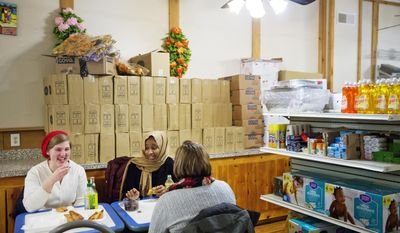 ADVANCE FOR USE WEDNESDAY, APRIL 19, 2017 AND THEREAFTER-Victoria Schalk, 22, left, and Melinda Blais, 27, right, share a traditional Somali meal with college classmate Nasteho Issa, 21, at restaurant and market opened by one of the first Somali families who settled in 2001 in Lewiston, Maine, Wednesday, March 15, 2017. The population had plummeted in 2001 as the paper mills closed. Downtown storefronts sat boarded up, ringed by sagging apartment buildings no longer needed to house workers since so few remained. The refugees saw possibility in Lewiston's decay. Word spread quickly and friends and families followed, by the hundreds. The town morphed in a matter of months into a laboratory for what happens when demographics and culture suddenly shift. (AP Photo/David Goldman)